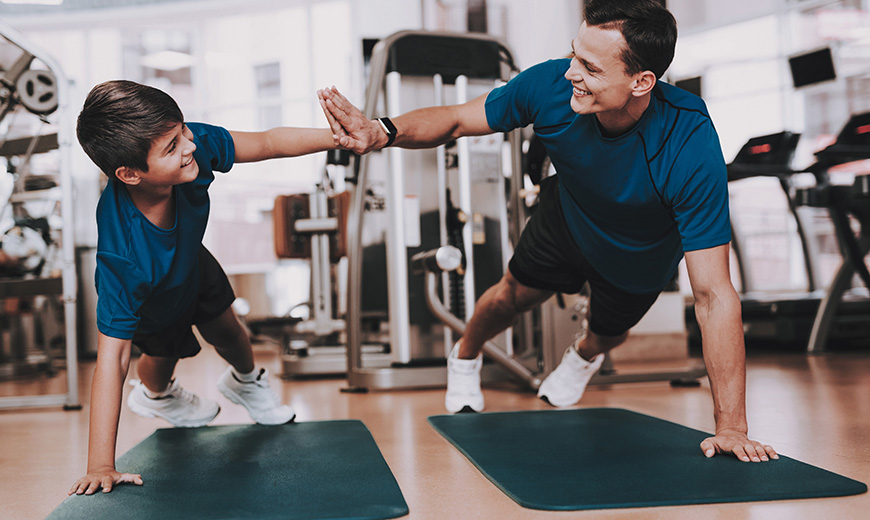 Young Father and Son Doing Exercises in Sport Club