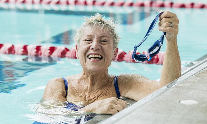 Senior woman in pool taking break from swimming laps